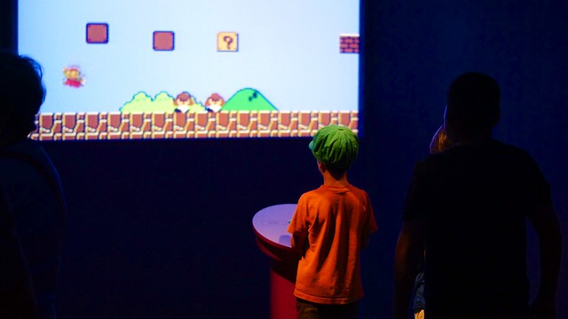 Child playing Super Mario Bros on a projection screen