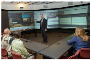 This image shows a moderator in the Decision Theater operating the DroughtSim interface with participants in the room.