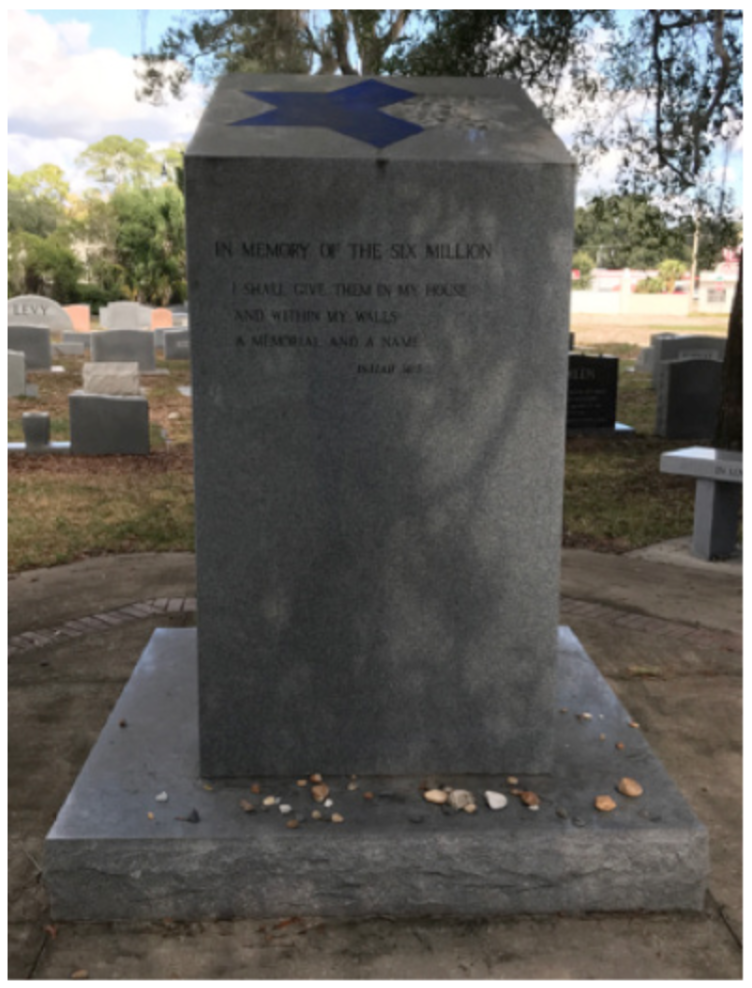 The Gainesville Holocaust memorial covered in stones by mourners. A two-thirds completed Star of David is displayed at a slant atop the pillar.