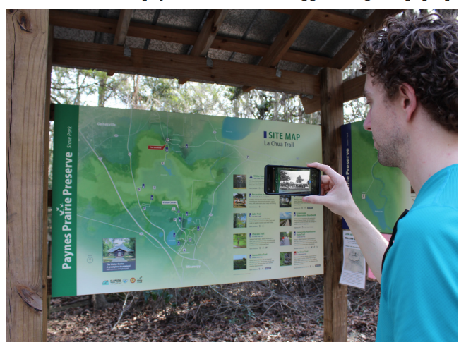 An image of a person using the augmented reality smartphone application. In the foreground, a phone is displaying digital content that has been triggered by scanning the map of Paynes Prairie in the background.